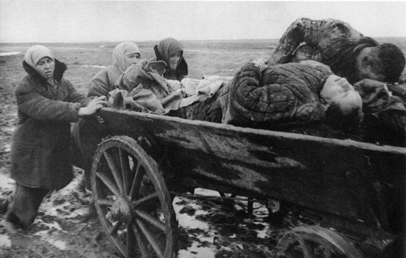 sovetskie zhenwiny tolkajut telegu s telami rasstreljannyh nemcami muzhchin