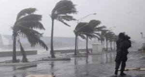 A man walks along the waterfront as Hurricane Irene passes to the east of Nassau on New Providence Island in the Bahamas, Thursday Aug. 25, 2011.  Irene is pounding the Bahamas as a Category 3 hurricane. (AP Photo/Lynne Sladky)